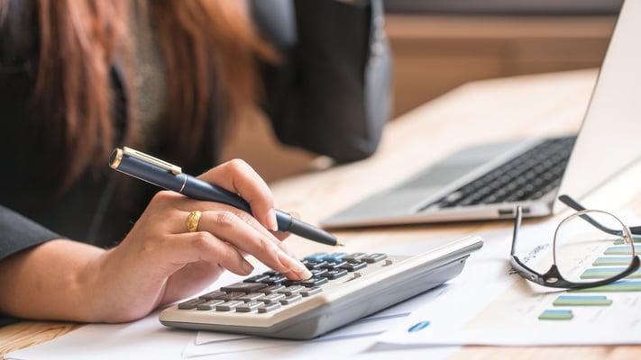 Tidkrevende manuelle regnskapsrutiner med kalkulator kan effektiviseres med automatisering.