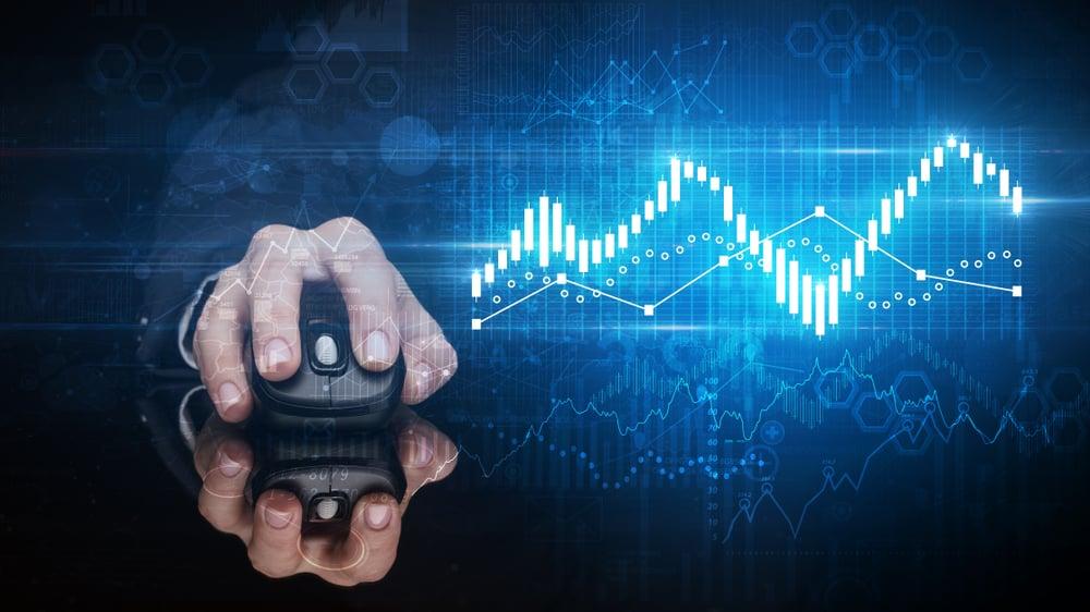 Hånd håndterer datamus på blank overflate med digitale økonomiindekser i bakgrunnen.