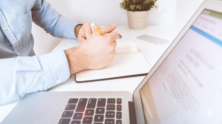 Norian gir svar på sentrale spørsmål som borettslag og sameier har rundt korona-krisen, illustrert med mann ved skrivebord med notatbok og laptop.